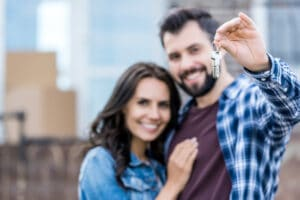 House keys in focus, smiling couple in blurry background
