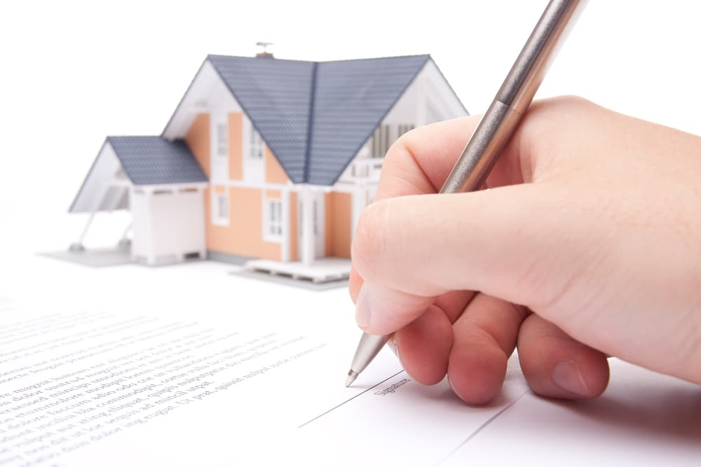 Close-up of hand signing paper, house model in background