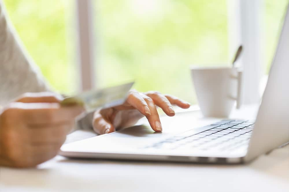 Close-up of woman holding credit card and typing on laptop